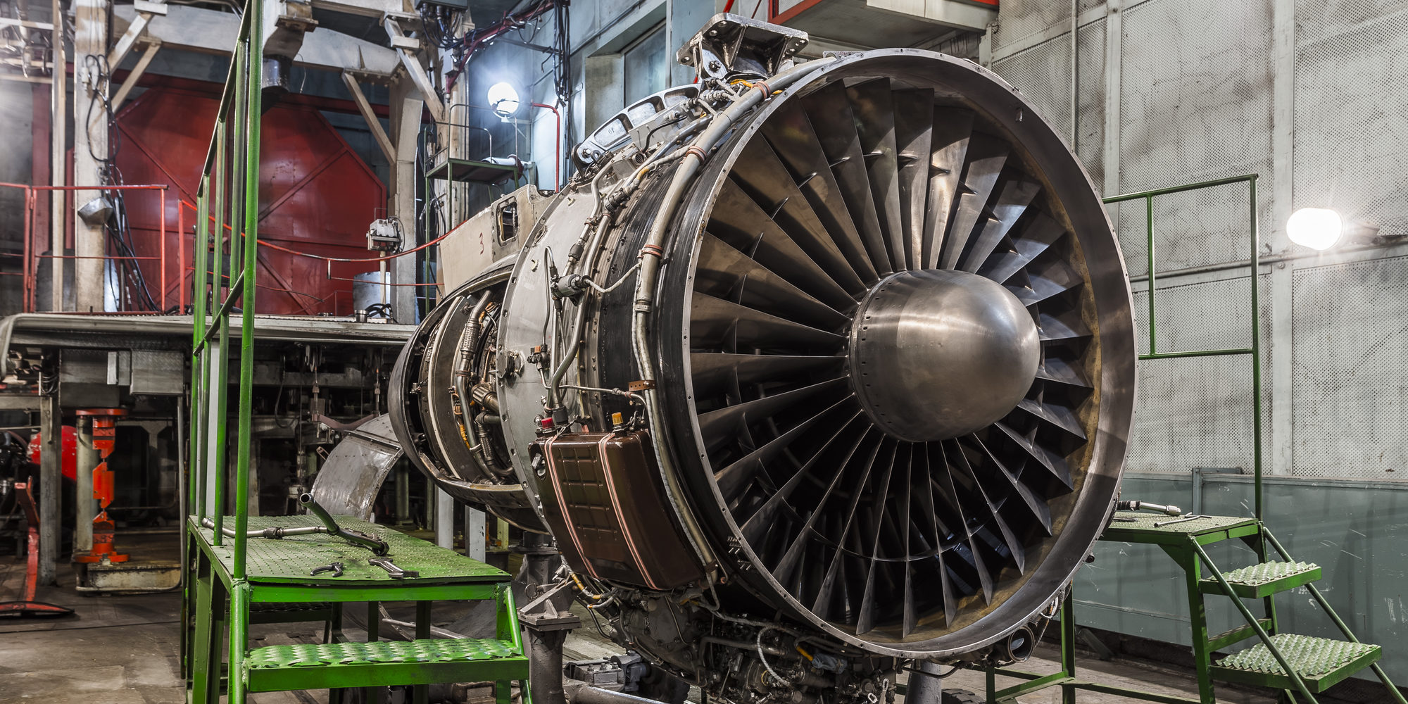 Airplane gas turbine engine detail in aviation hangar. Plane rotor under heavy maintenance.